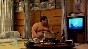 Un sumotori devant la télévision