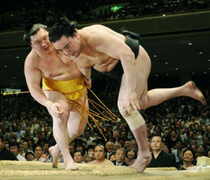 Hakuhô portait une ceinture mawashi en or inspirée de Wajima après avoir égalé l'ancien yokozuna avec un 14e titre au Summer Basho 2010. (avec l'autre yokozuna Harumafuji)